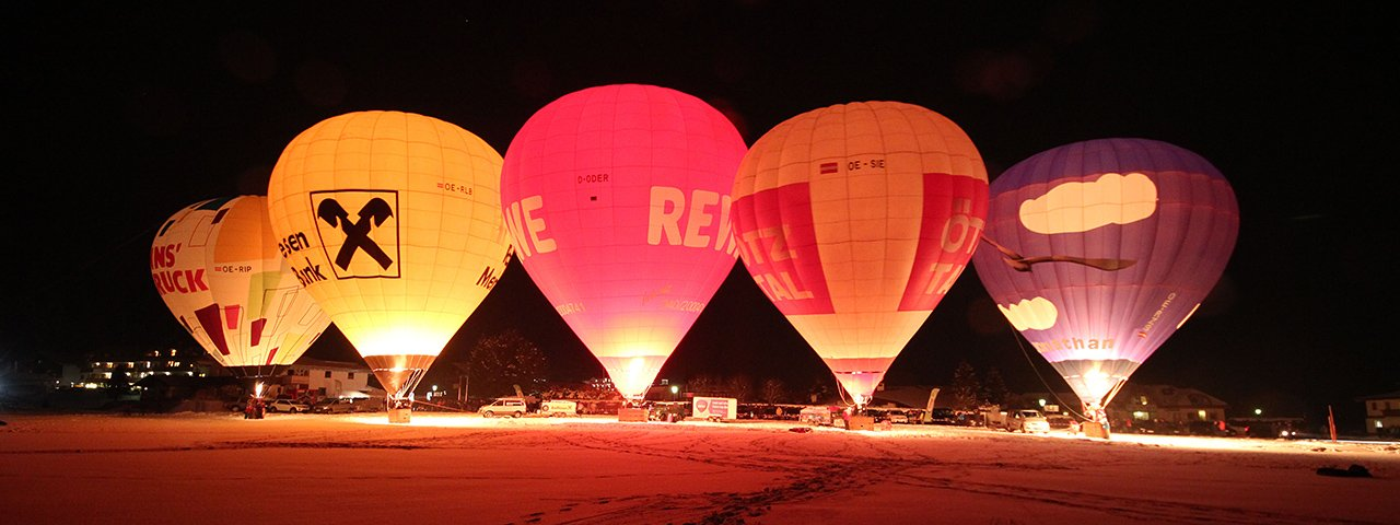 Rows of bulbous luminaries, dozens of feet tall, lit up from the glow of flames: The Night Glow during the Achensee International Balloon Days, © Stephanie Vetter / Achensee Tourismus