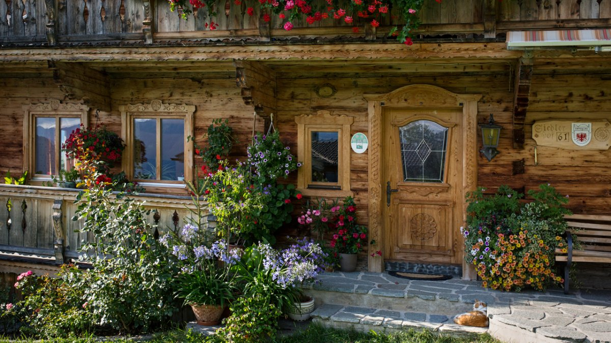 This 19th century farmstead is richly decorated in spring and summer like many other farms in the Brixental Valley., © Tirol Werbung/Lisa Hörterer