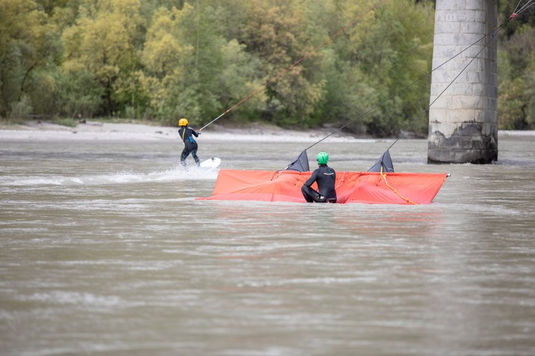 Thanks to a submerged, orange coloured underwater sail, surfers can ride river waves in Tirol.