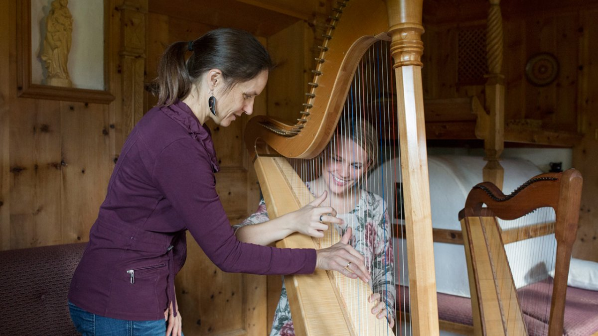 Annemarie Fritz teaches at the local music school and offers her guests the chance to play the harp., © Tirol Werbung/Lisa Hörterer