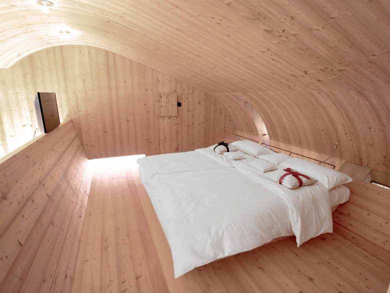 The interior decor of the Ufogel is modern and very minimalist: Sleeping in a Swiss stone pine wood bed underneath a domed roof. Photo Credit: Thomas Pitterl