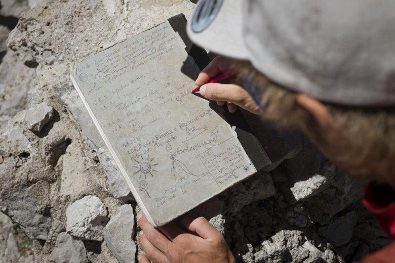 Mountain guide Guido Unterwurzacher signing the summit book on Wilder Kaiser Mountain.