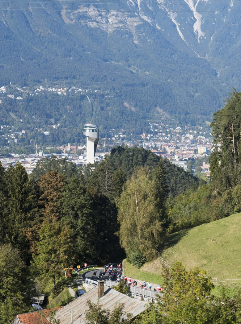 The peloton on the descent to Innsbruck, towered by Bergisel Ski Jump.