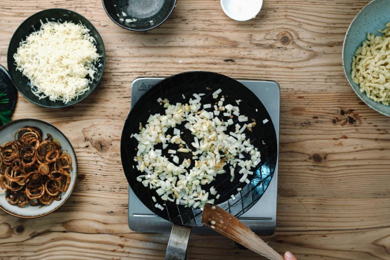 Step 4: In a pan, sauté the diced onion with a knob of butter, add the spätzle and stir in the cheese in small batches. Mix well and allow the cheese to melt.
