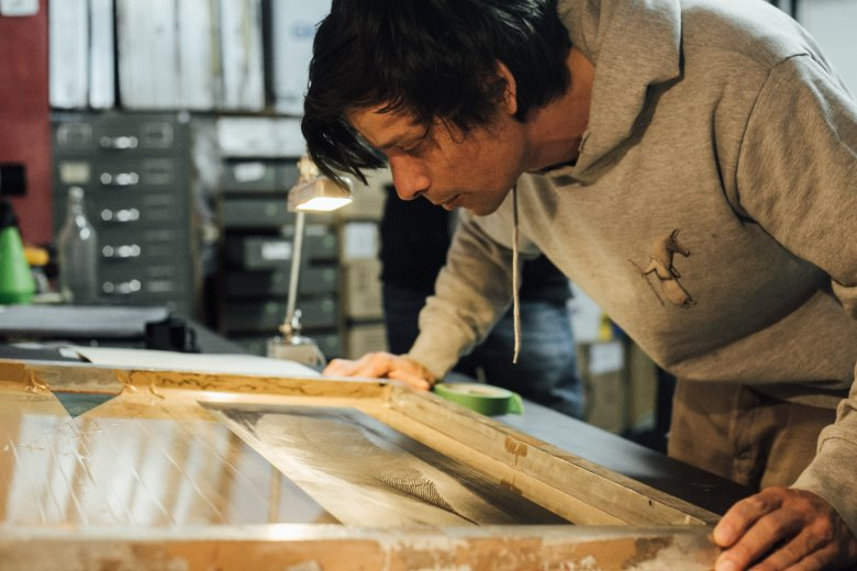 Lukas uses the screen printing method to create unique topsheets for Benoît's snowboards.