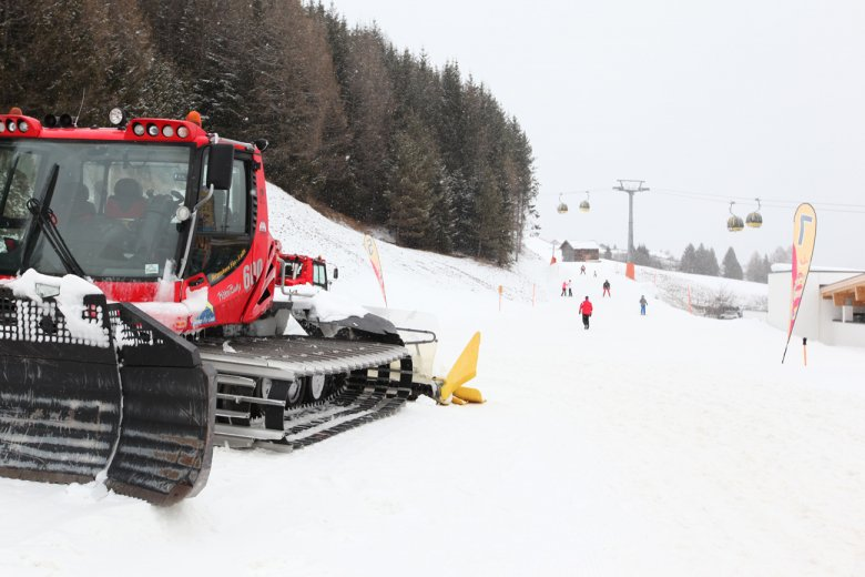 When the ski slope groomer teams start preparing and polishing the snow, there are still skiers making their last run.