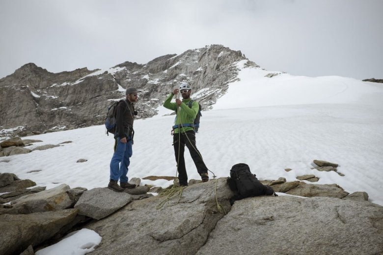 Roping-up for glacier travel. Depicted in the rear is the summit ridge.