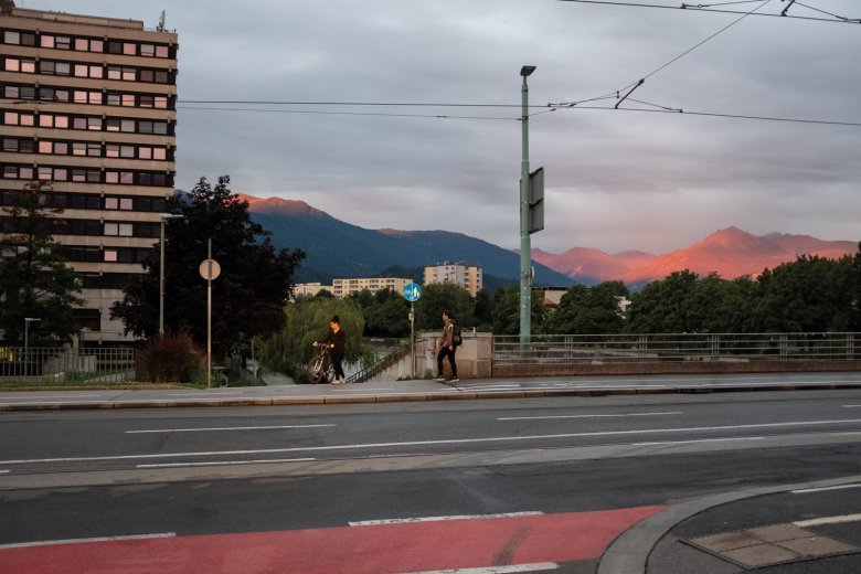 6.50 A.M. Things are still quiet on Innsbruck's University Bridge as the mountains behind glow in the early-morning sun.