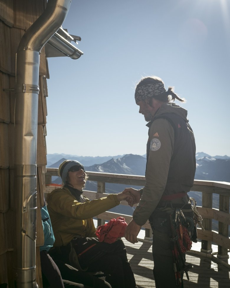 Mountain guide Matthias Wurzer (pictured to the right) greets a friend at Adlersruh Hut on Großglockner Mountain.