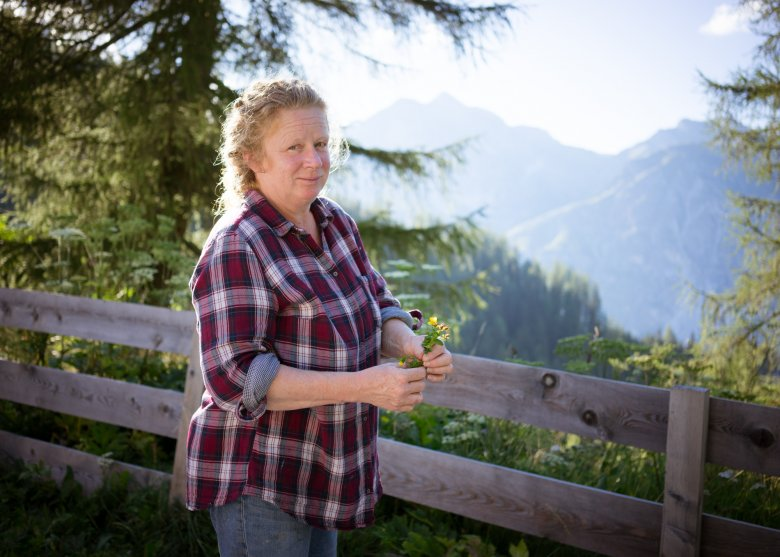 Ingrid Schlögl, who runs the Trunahütte, collects herbs in the area around the hut.