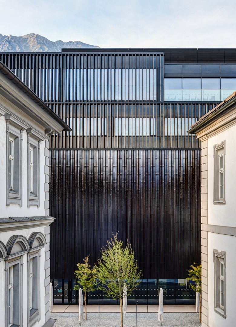The façade is clad with dark ceramic panels that change its color during the day as the sun is shining from a different angle.