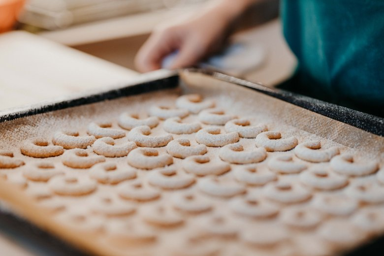 While the cookies are still hot and on the baking tray, sprinkle them through a sieve with the mixture of vanilla sugar and icing sugar. Then leave to cool off.