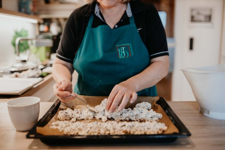 Mix the eggs and sugar into a cream, then fold in the flour. Add the nuts and raisins. Stir it all together and add water as necessary until you can place the mixture into a long sausage-like shape on the baking tray. Put into the oven for around 20 minutes at 180°C.