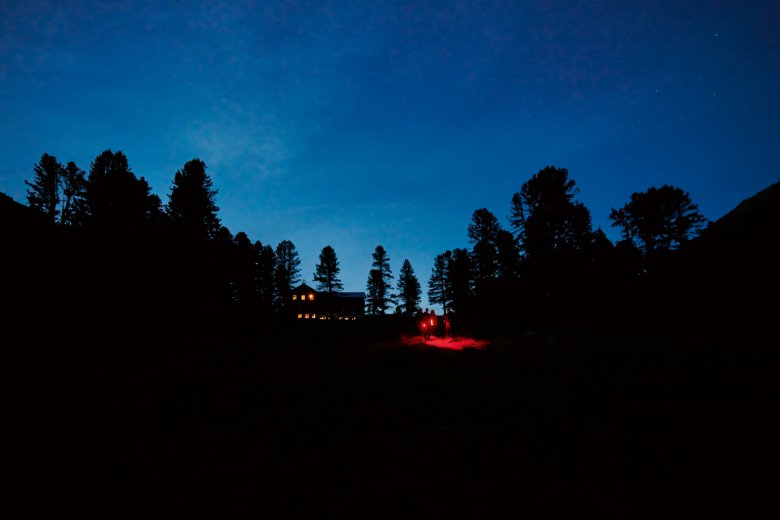 Night hikers exploring the Ötztal Valley Alps with their red-light torches.