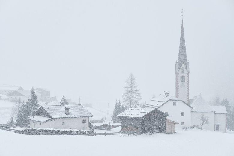 Snow falls on the parish church at St. Sigmund im Sellrain.