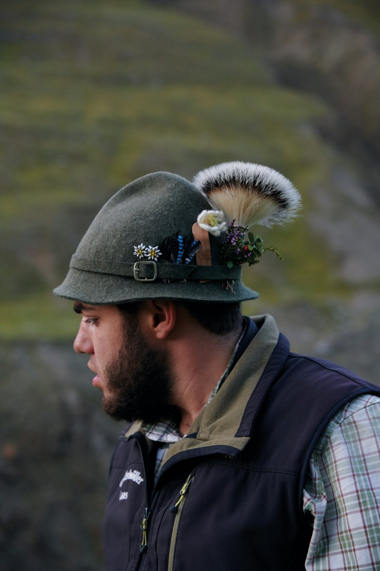 Gentian, Mountain Arnika, and Alpine Roses blossom and wither on the hats of the shepherds. Edelweiss flowers made out of felt and evergreen shrubbery stay on the hat.