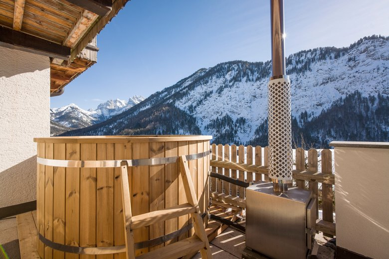 Berg'k'hof – Wooden outdoor tub with view of the rugged Kaiser Range. Photo Credit: Hannes Dabernig