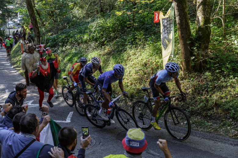 """The leaders heading into the foot of the dreaded """"Höll"""" climb, cheered up by legendary Didi Senft, the Tour Devil, and devilish creatures from Tirol called """"Krampus""""."""