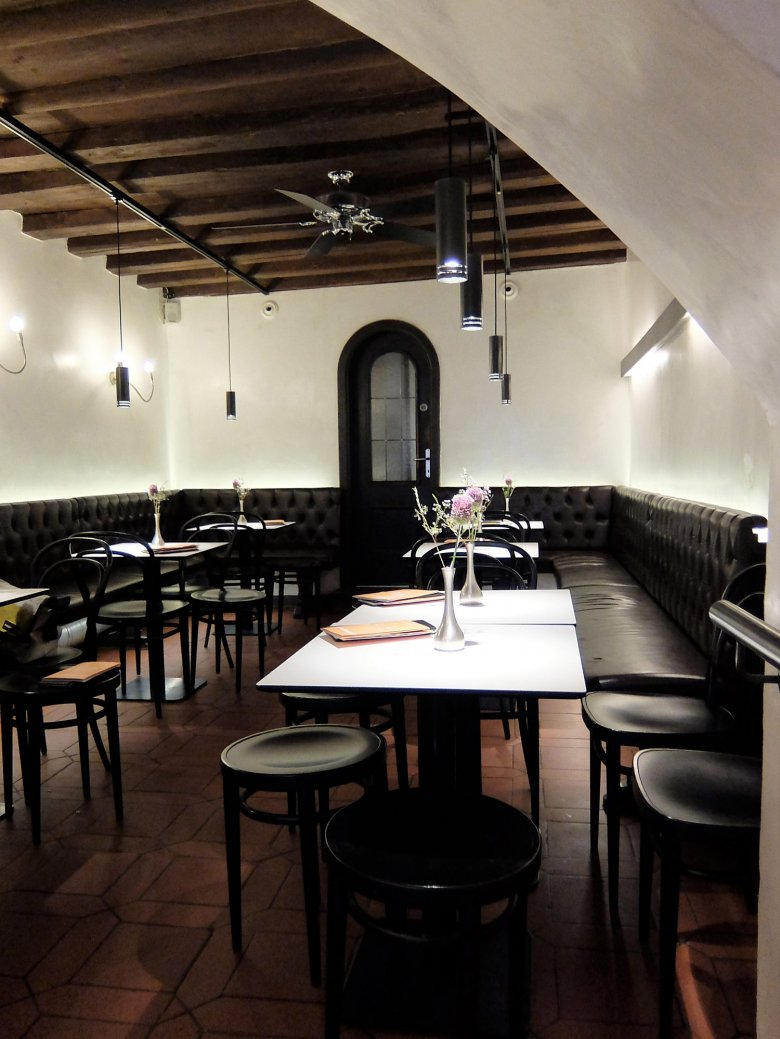 The inside of the Café is reminiscent of an elegant wine cellar, complete with stone walls and a rounded ceiling.