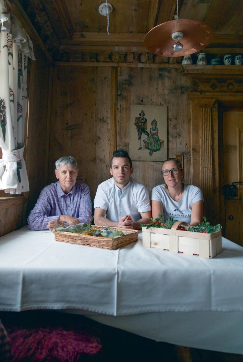Michael Ploner, Rose-Marie and Barbara Waldegger sort through the result of their foraging adventure in the old parlour room at the Hotel Central.